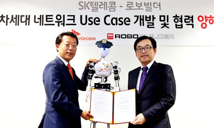 SK Telecom Chief Technology Officer Choi Jin-sung, right, poses with Park Chang-bae, CEO of RoboBuilder, after signing an agreement to work together to develop 5G robots, which are controlled through fifth-generation network technology, at SKT's office building in Seoul, Thursday. / Courtesy of SKT