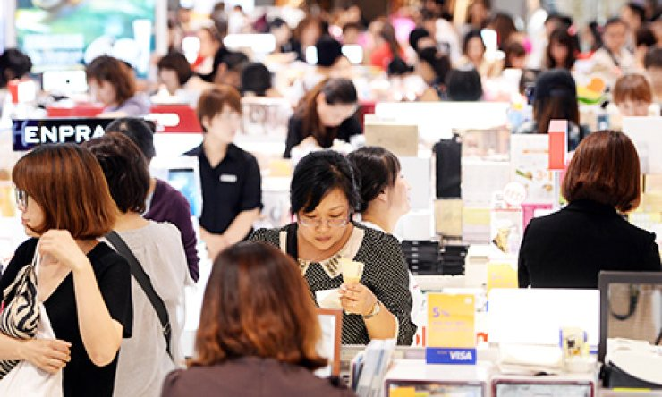 Shoppers crowd a duty free store in Seoul. Seven big companies are vying to win the licenses to run two new duty free stores in Seoul. / Korea Times file