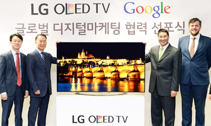 Kim Ki-wan, second from left, president of home entertainment overseas sales and marketing group at LG Electronics, poses with John Lee, second from right, country director of Google Korea, after signing an agreement to promote LG's OLED TVs in the global market, at Google Korea's office building in Seoul, Tuesday./ Courtesy of LG Electronics