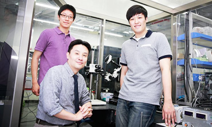 Material Science and Engineering Professor Park Jang-ung, center, poses with his research team at his laboratory in Ulsan National Institute of Science and Technology (UNIST) in Ulsan, southeast of Seoul, Tuesday. The institute said Park's research team has developed an improved three-dimensional printing technology./ Courtesy of UNIST