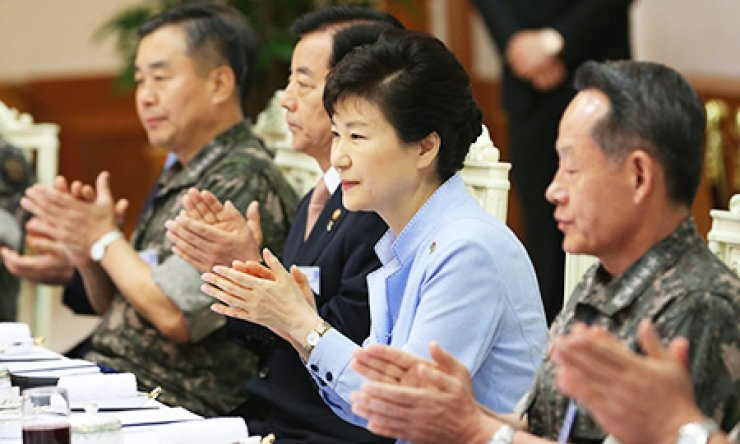 President Park Geun-hye claps during a meeting with Defense Minister Han Min-koo, third from right, and top military commanders at Cheong Wa Dae, Tuesday./ Yonhap