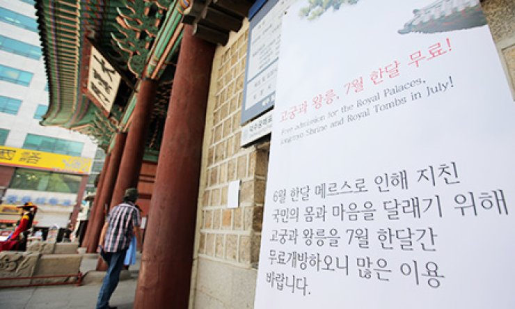 A poster at the entrance of Deoksu Palace in central Seoul reads Wednesday that free admission is available for the capital's four palaces, the Jongmyo Shrine and Royal Tombs in July. The free admission is part of the government effort to revitalize the nation's tourism industry, which has been hit hard by the Middle East Respiratory Syndrome epidemic. / Yonhap