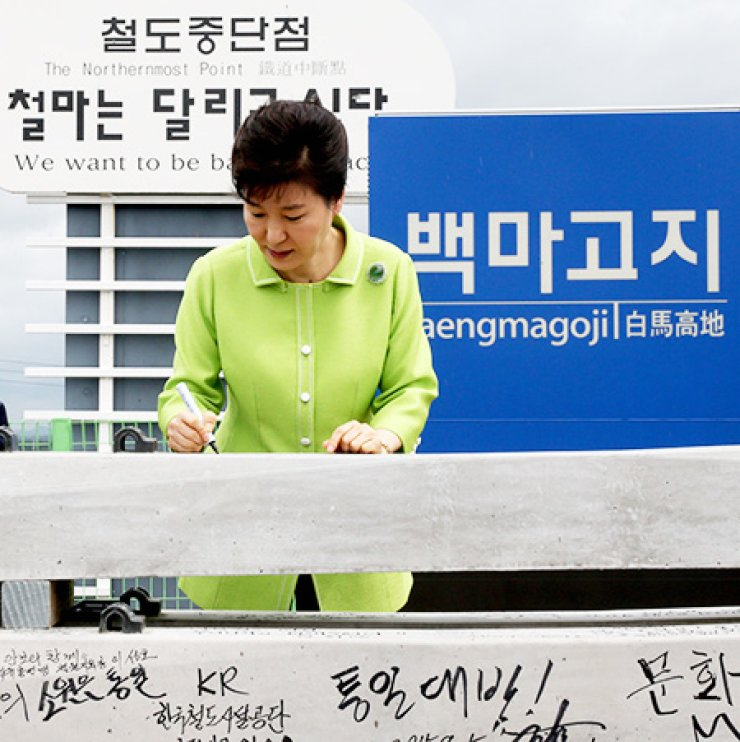 President Park Geun-hye writes on a railroad sleeper during a ceremony at Baengmagoji Station in Cheorwon, Gangwon Province, Wednesday, to launch a project to restore the South Korean section of the 223.7 kilometer Gyeongwon Line, a disconnected inter-Korean railroad. / Courtesy of Cheong Wa Dae press corps
