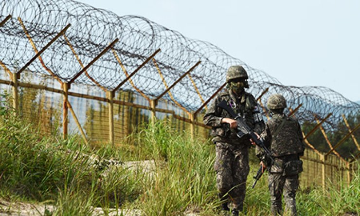 Armed South Korean soldiers patrol along a barbed-wire fence in the Demilitarized Zone, Monday. / Yonhap