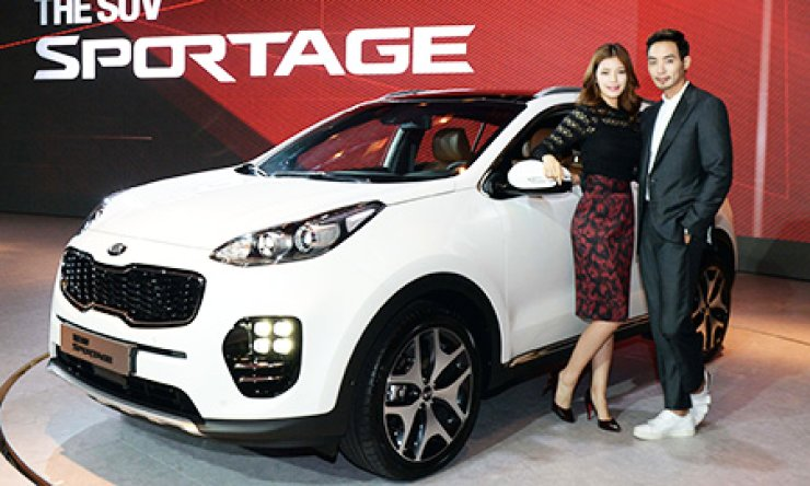 Models pose next to Kia Motors new Sportage compact SUV, during a launch event at the W Hotel in Seoul, Tuesday. / Courtesy of Kia Motors