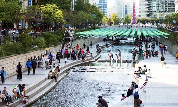 People walk alongside Cheonggye Stream, central Seoul, Tuesday. Thursday marked the 10th anniversary of the stream's restoration. / Yonhap