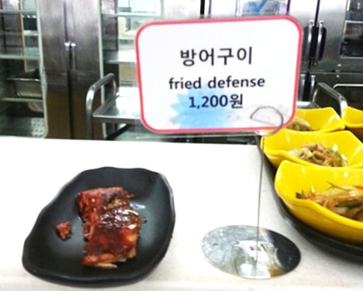 A menu tag describes fried yellowtail as 'fried defense' in this photo taken at an unidentified restaurant in 2013. Yellowtail is pronounced in Korean 'Bang-uh,' which also means defense. Such mismatched Korean-English translations are found on many restaurant menus. / Korea Times file