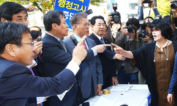 The main opposition New Politics Alliance for Democracy Chairman Rep. Moon Jae-in, fourth from left, and other lawmakers argue with members of conservative civic groups during the party's signature-collecting campaign in Yeouido, Seoul, Tuesday, to protest state-authored history textbooks. / Korea Times photo by Oh Dae-geun