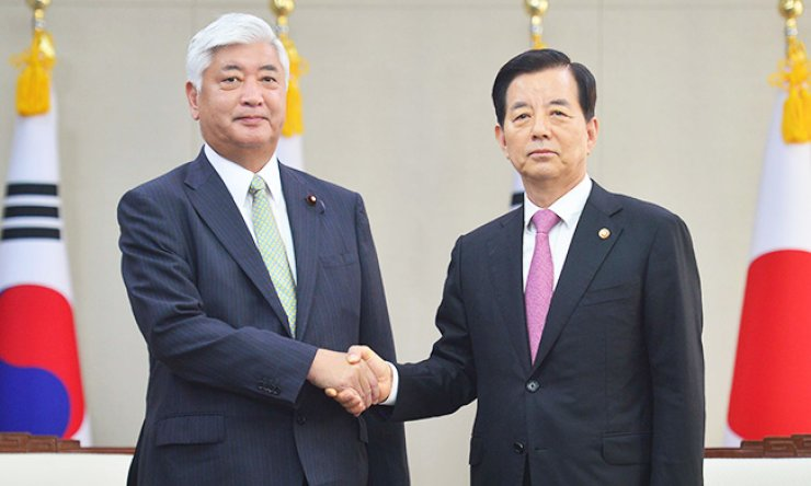 Defense Minister Han Min-koo, right, shakes hands with his Japanese counterpart Gen Nakatani ahead of their talks at the Ministry of National Defense in Seoul, Tuesday. / Yonhap