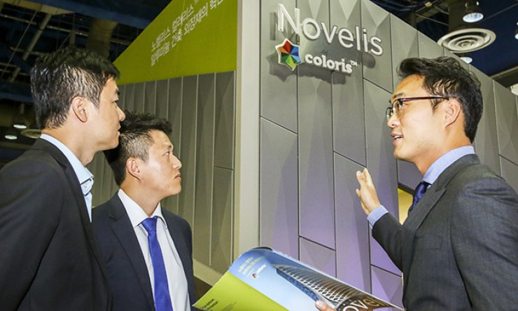 A Novelis Korea employee, right, talks about the firm's latest aluminum-based construction materials in front of its promotional booth during the Korea Architecture Fair and Festival at the COEX, southern Seoul, Monday./ Courtesy of Novelis Korea