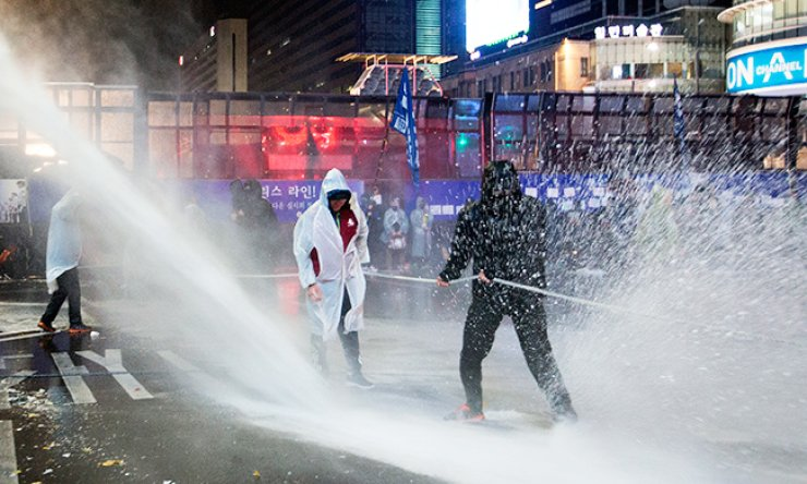 Police fire water cannon at protestors who used a rope to try and topple a police bus during an anti-government protest held in Gwanghwamun Square, central Seoul, Saturday. / Korea Times photo by Choi Won-suk