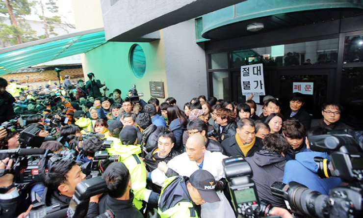 Police officers try to forcibly remove temple officials from the entrance of a building on the grounds of Jogye Temple in central Seoul, Wednesday, where Korean Confederation of Trade Unions (KCTU) head Han Sang-gyun has taken refuge to avoid arrest. / Yonhap