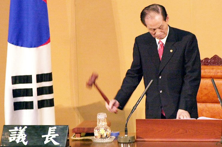 Former National Assembly Speaker Lee Man-sup bangs the gavel in this September 2001 file photo to proclaim the dismissal of then Unification Minister Lim Dong-won. Lee passed away Monday at age 83. / Yonhap