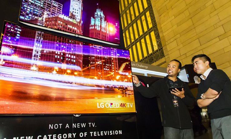 Visitors watch LG Electronics' OLED TVs at its exhibition booth in Grand Central Station, New York, early this month./ Courtesy of LG Electronics
