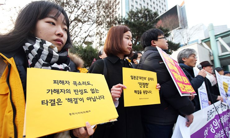 Members of civic groups hold a rally outside the headquarters of the foreign ministry in Seoul, Tuesday, in protest against the deal between Korea and Japan on the comfort women issue. / Yonhap