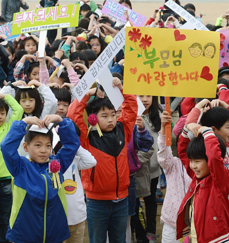 Students of Gwangmyeong Elementary School make heart shapes with their arms, expressing their love for their parents in celebration of Parents' Day on May 8 at a traditional market in Gwangmyeong, Gyeonggi Province. / Korea Times