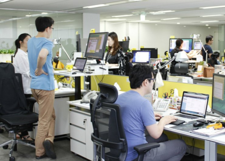 Employees at local IT firm Kakao work on their height-adjustable desks at its headquarters in Pangyo Techno Valley, Bundang, Gyeonggi Province. More people are opting to work on their feet, as the benefits of standing-desks at workplaces gain recognition. / Courtesy of Kakao