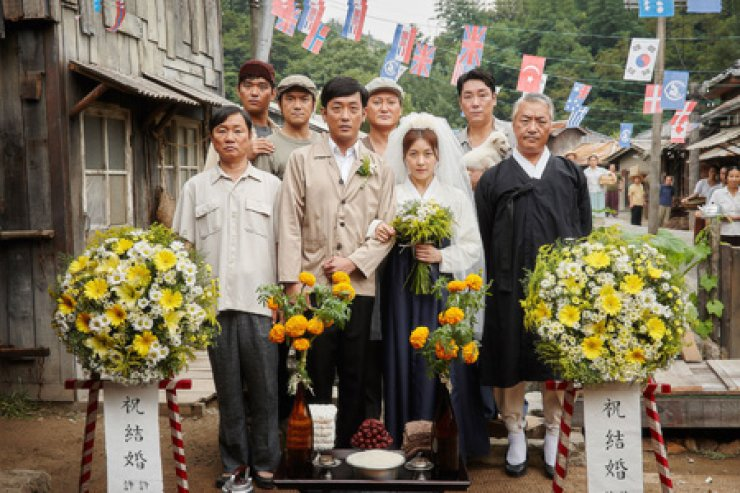 ctor Ha Jung-woo, second from left in the front row, and actress Ha Ji-won, to his left, in a scene from 'Chronicle of a Blood Merchant' / Courtesy of NEW