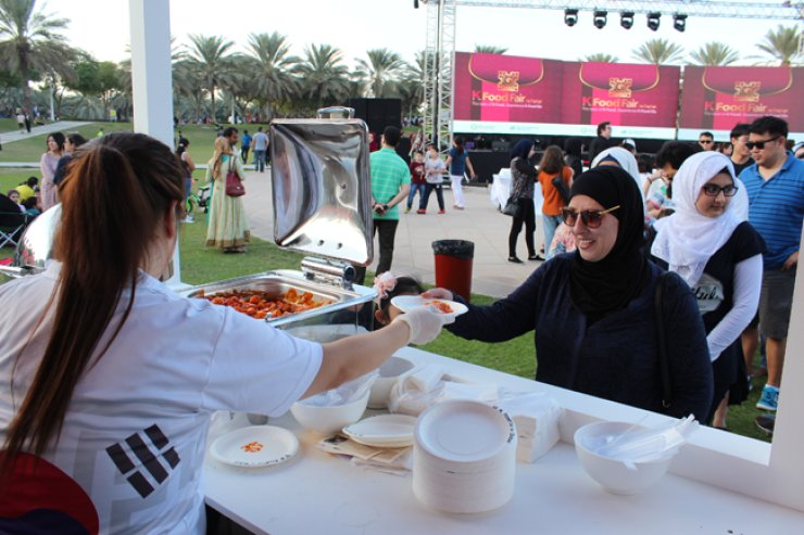 A visitor to the K-Food Fair in Dubai receives 'tteokbokki,' or spicy stir-fried rice cake, Nov. 28.  / Yonhap