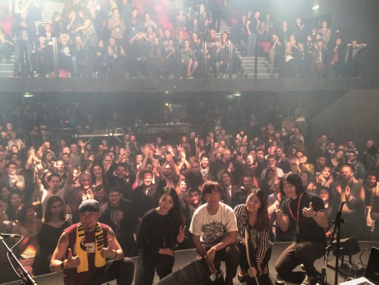 Members of indie band Jambinai - Sim Eun-yong, second from left, Lee Il-woo, center, and Kim Bo-mi, second from right - join with members of the audience after a performance in Europe.  / Courtesy of Jambinai