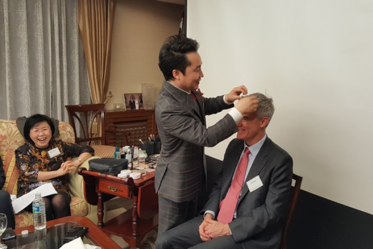 The CEO of Ra Beauty Core Kim Hyun-tae, center, styles the hair of Bill Miner, Country Chairman of Chevron, at the residence of Kuwaiti Ambassador Jasem Albudaiwi in Yongsan-gu, Seoul, Tuesday./ Korea Times photo by Kim Jae-heun