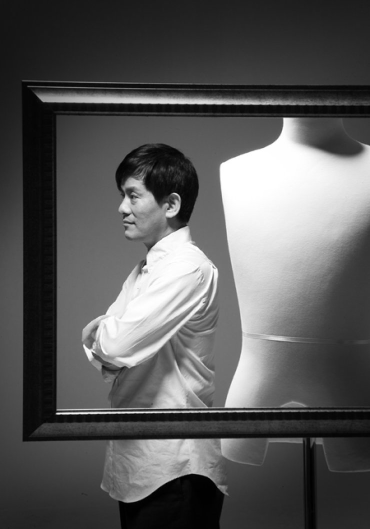 Veteran designer Chang Kwang-hyo poses behind a frame. / Courtesy of Caruso by Chang Kwang-hyo