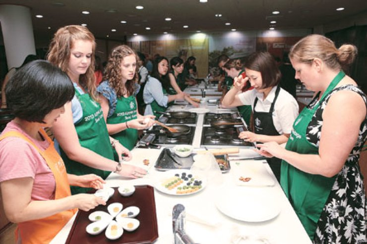 Starbucks promotes Korean culture: Foreigners make a traditional cookieat Korea House, an upscale Korean food restaurant in downtown Seoul,Tuesday. Starbucks Coffee Korea hosted the event to celebrate the firm's 14th anniversary in Korea, in cooperation with the Korea Cultural HeritageFoundation. Four more sessions will be held at the restaurant through Aug. 20./  Courtesy of Starbucks Coffee Korea