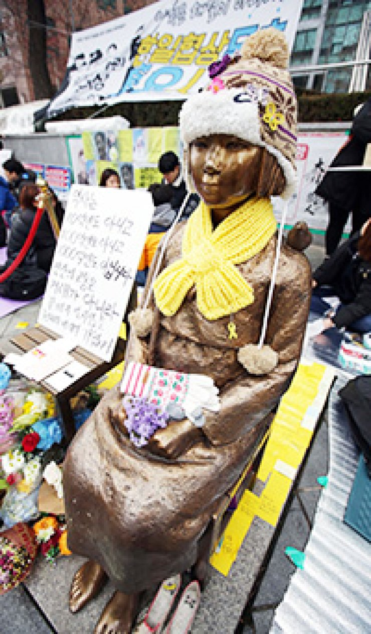 The statue of a girl, a symbol of Korean sex slavery victims during World War II, stands in front of the Japanese Embassy in Seoul. While former sex slaves oppose the Dec. 28 agreement between Korea and Japan on Japan's apology and fund offering to solve the issue, government-authored textbooks are likely to describe the issue according to the deal. / Yonhap