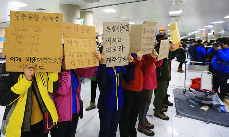 Passengers of Jeju Air demand that the carrier operate more flights after a massive number of flight cancellations followed heavy snowfall at Jeju International Airport, Monday. / Yonhap