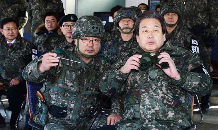 Saenuri Party Chairman Kim Moo-sung, right, listens to the commander of the 6th Infantry Division during his visit to a general post near the border in Cheorwon County, Monday. / Joint press corps