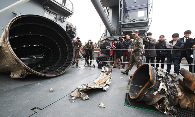 Four pieces of debris from North Korea's long-range rocket, retrieved off Eocheong Island in the West Sea, are displayed on the salvage vessel Tongyeong at Pyeongtaek Port, Gyeonggi Province, Thursday. The dented cylindrical object on the left is believed to be the fairing connecting the rocket's first and second stages, while the other pieces are presumed to be parts of a combustion gas jet nozzle. / Yonhap