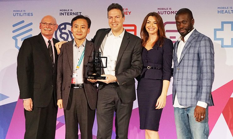 Shim Sang-soo, second from left, the head of SK Telecom's network business division, holds a trophy with Accedian CEO Patrick Ostiguy, center, after SKT was named the Best Technology Enabler at the GSMA Global Mobile Awards in Barcelona, Spain, Tuesday (KST). / Courtesy of SK Telecom