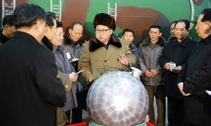 North Korean leader Kim Jong-un speaks to scientists standing in front of a silver, round-shaped object, presumed to be a mockup of a miniaturized nuclear warhead, in a photo published Wednesday by Pyongyang's Rodong Sinmun. / Yonhap