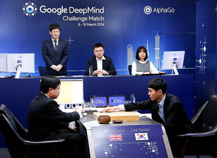 Korean professional go player Lee Se-dol, right, plays against the artificial intelligence system AlphaGo during the Google DeepMind Challenge Match at the Four Seasons Hotel in central Seoul, Wednesday. On the left is DeepMind's lead programmer Aja Huang putting stones on behalf of AlphaGo. / Courtesy of Google Koea