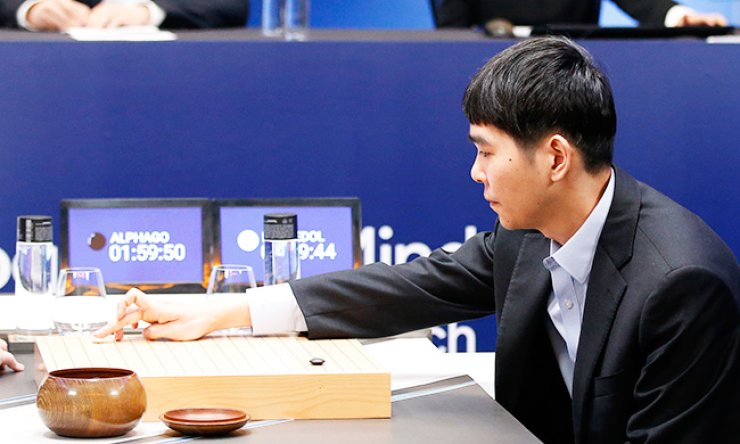 World go champion Lee Se-dol makes his first move against Google's artificial intelligence program, AlphaGo, during the second game of the Google DeepMind Challenge Match in Seoul, Thursday. / AP-Yonhap