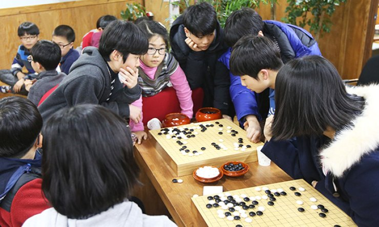 Students play 'go' - 'baduk' in Korean - at Lee Se-dol's baduk academy in Seoul, Thursday, when the second match between Lee and AlphaGo was played. / Yonhap