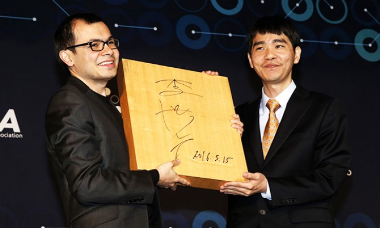 World go champion Lee Se-dol, right, presents a go board with his autograph to DeepMind CEO Demis Hassabis after the final game of the Google DeepMind Challenge Match at the Four Seasons Hotel in central Seoul, Tuesday./ Korea Times photo by Hong In-ki