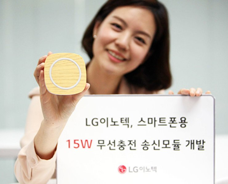 A model promotes a wireless smartphone charger with LG Innotek's 15-watt wireless power transmission module in this file photo. The company said the new module can charge 50 percent of an empty battery within 30 minutes, as fast as a wired charger. / Courtesy of LG Innotek