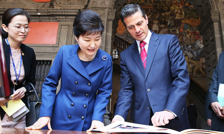President Park Geun-hye and her Mexican counterpart Enrique Pena Nieto look at a photo album after their summit at the National Palace in Mexico City, Mexico, Tuesday. The photo album was a gift from PresidentPena Nieto to Park. / Joint press corps