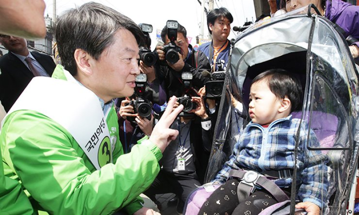 Rep. Ahn Cheol-soo, co-chairman of the minor opposition People's Party, talks to a child during a campaign event in Uijeongbu, Gyeonggi Province, Tuesday, for the April 13 general election. / Yonhap