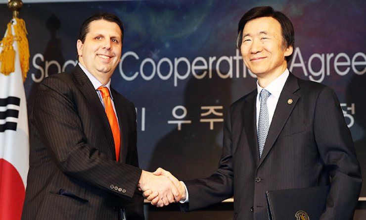 Foreign Minister Yun Byung-se, right, shakes hands with U.S. Ambassador to South Korea Mark Lippert after signing an agreement on joint space exploration at The Plaza Hotel Seoul, Wednesday. / Yonhap