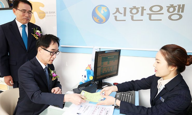 Deputy Prime Minister and Minister of Education Lee Joon-sik, sitting on the left, participates in a banking transaction experience program offered by Shinhan Bank for grade school students in rural areas. / Courtesy of Shinhan Bank