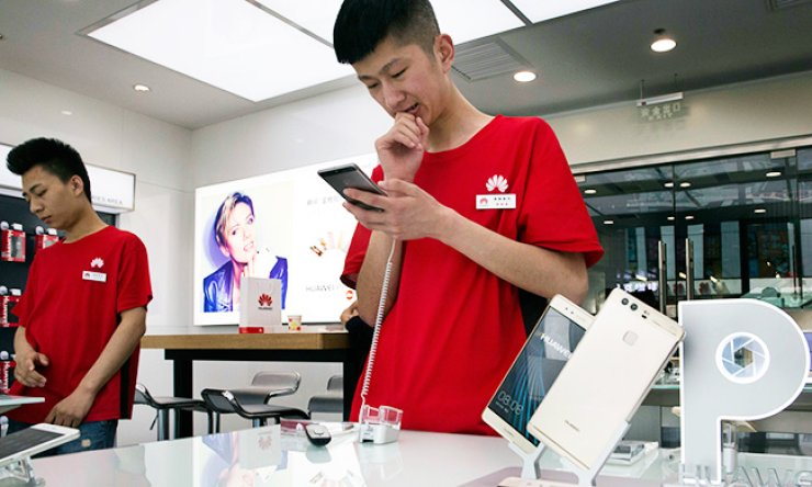 Chinese sales representatives wait for customers at a Huawei retails shop in Beijing. / AP-Yonhap