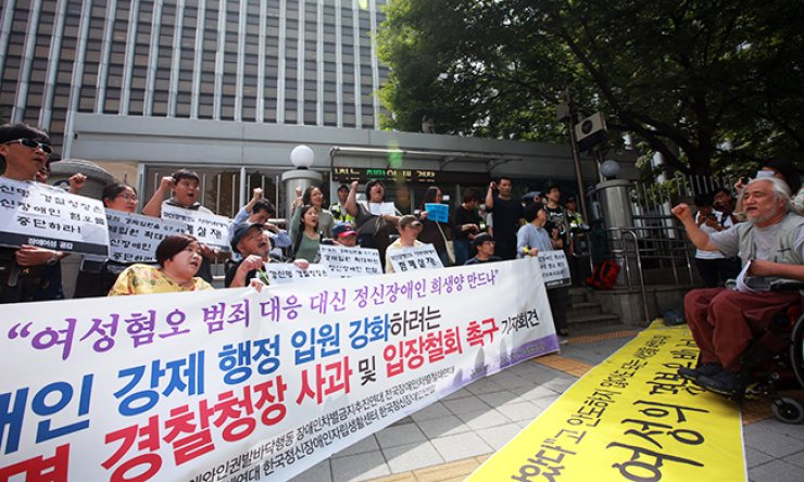 Disabled activists sit in front of the National Police Agency in Seoul in protest of the police association over the recent Gangnam murder committed by a man with mental illness, Friday. They claimed not all mentally ill people are murderers, and that the Gangnam incident was a clear hate crime against women, demanding an apology from the police./ Yonhap