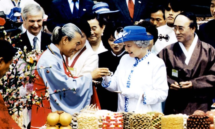 Queen Elizabeth II celebrates a toast with a Buddhist monk during her 73rd birthday at the traditional village of Hahoe in Andong, North Gyeongsang Province, in 1999. / Korea Times file