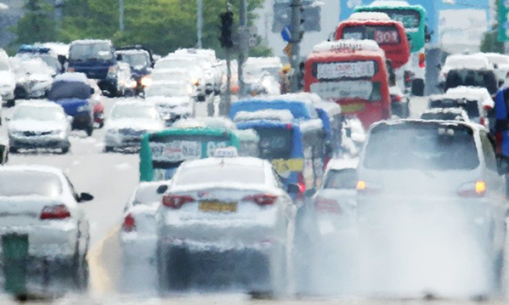Cars emit exhaust gases on a road in Yeouido, Seoul, Friday. Environment Minister Yoon Seong-kyu announced measures to reduce Korea's fine dust level, including replacing all diesel buses in the country with natural gas-powered ones and shutting down old coal-fired power plants. / Yonhap