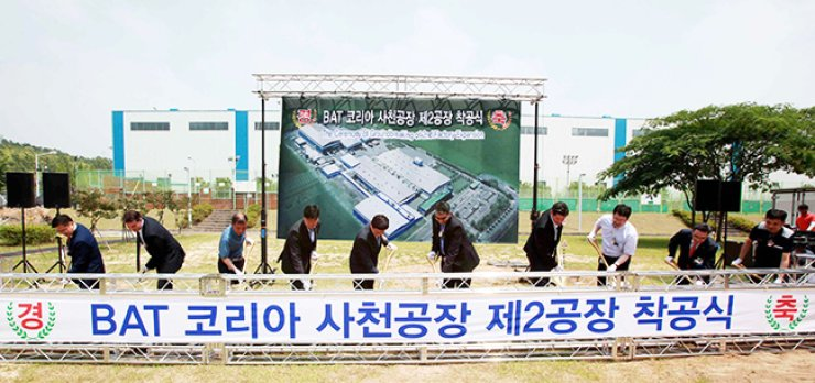 BAT Korea Vice President Bae Yoon-suk, left, breaks ground with Sacheon City Mayor Song Do-keun, fifth from left, and other dignitaries at a groundbreaking ceremony for the company's second plant in Sacheon, South Gyeongsang Province, Friday. / Courtesy of BAT Korea