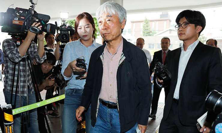 Artist Lee U-fan appears at the Seoul Metropolitan Police Agency, Wednesday, holding his workbook to confirm the National Forensic Service's decision earlier this month that some of his paintings had been counterfeited. / Yonhap