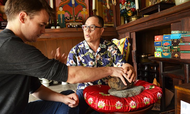 Yang Jong-sung, right, director of the Museum of Shamanism, directs a visitor through a shamanistic ritual using a 'dolhalmeoni' (grandmother stone), believed to have spiritual power to make people's wishes come true./ Korea Times photo by Jon Dunbar
