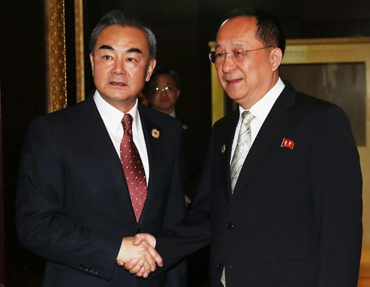 Chinese Foreign Minister Wang Yi, left, shakes hands with his North Korean counterpart Ri Yong-ho ahead of their talks in Vientiane, Laos, Monday. Wang strongly protested the planned deployment of a U.S. anti-missile system in South Korea during his talks with South Korean Foreign Minister Yun Byung-se a day earlier; and vowed to boost relations with North Korea at the meeting with Ri. / Yonhap
